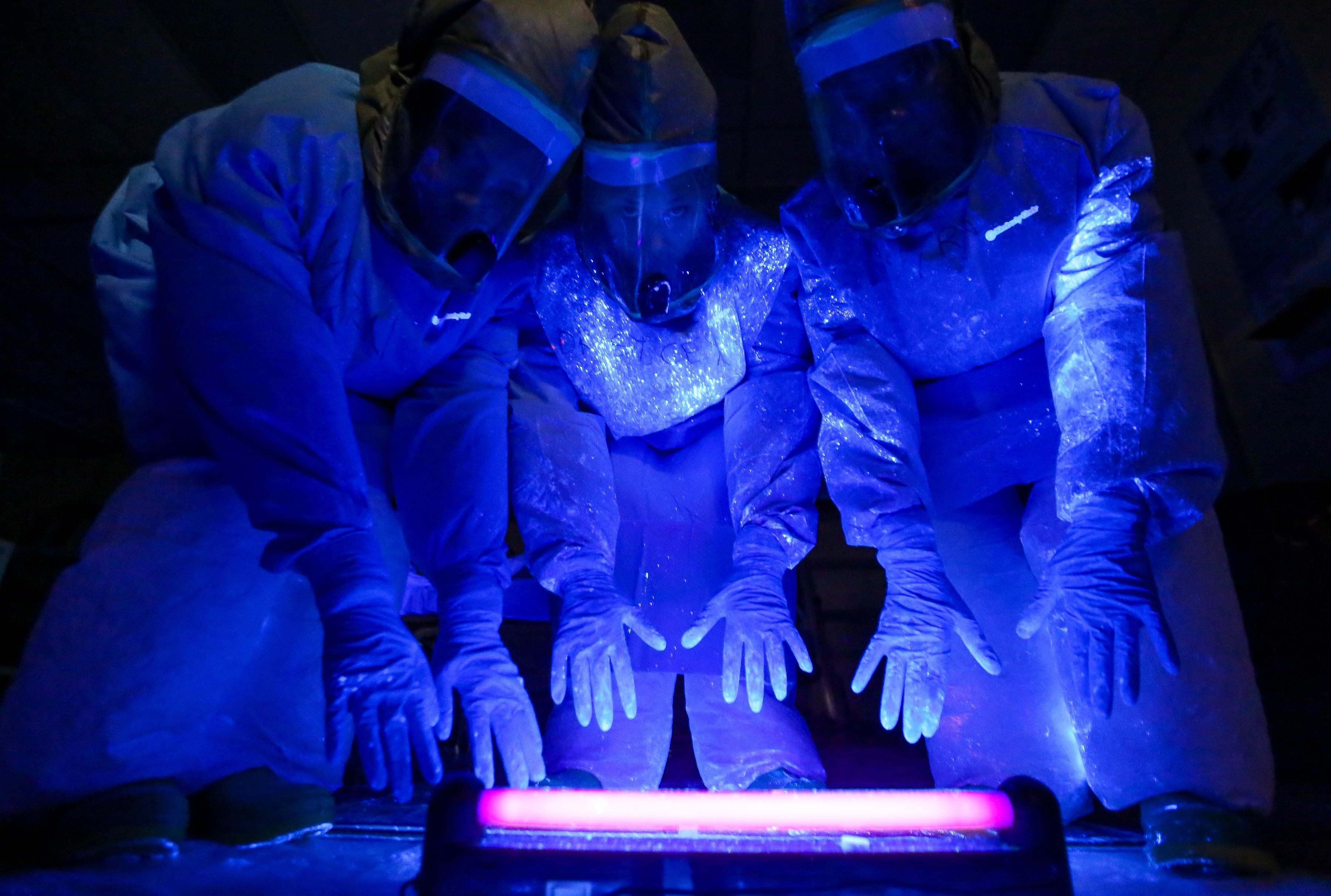 A black fluorescent light shows where simulated bodily fluid containing a mock Ebola virus landed on a care team's personal protective equipment, during a training exercise at Madigan Army Medical Center's Andersen Simulation Center, Nov. 6, 2014